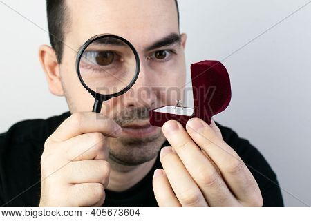 The Main Subject Is Out Of Focus, Man Hold Magnifying Glass Closeup Look At Ring Box, Expensive Or C