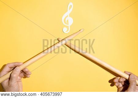 Drummer Concept. Male Hands Holding Drumsticks And A Paper Treble Clef And Musical Treble Clef. Flat