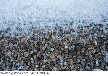 Small Gravel Road Covered In Snow Texture. Winter Pebble Background. Dirty Road. Fros Morning. Snowy