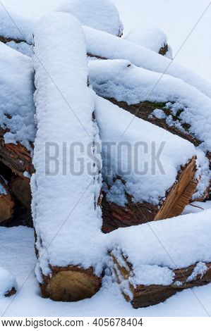 Stack Of Firewood Covered With Snow Outdoors. Stack Of Wood Cut. Snow On The Timber Stack. Wooden Lo