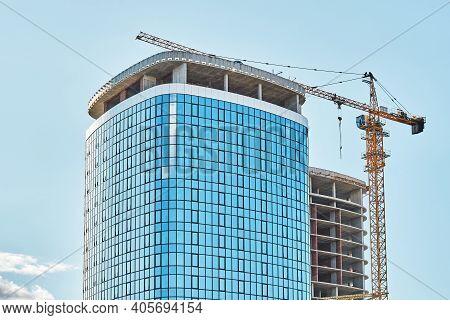 Crane Near Skyscraper With Glass Facade At Construction Site