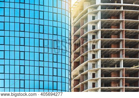 Skyscrapers With Blue Glass And Carcass At Construction Site