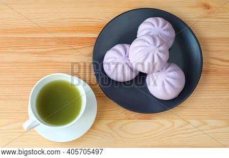 Cup Of Green Tea With A Plate Of Taro Steamed Buns On Wooden Table
