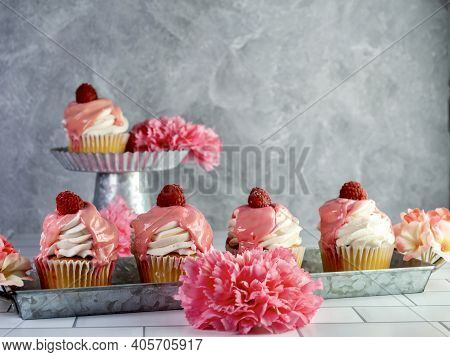 Raspberry Cupcakes With White Frosting And Pink Drizzle With A Fresh Raspberry On Top, Sitting On Ru