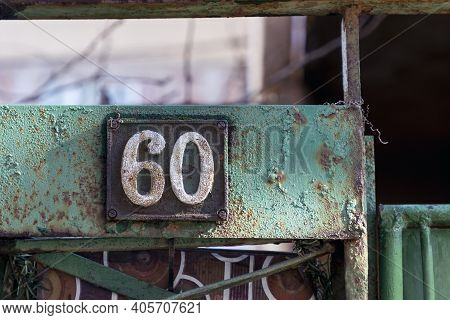 Number 60, The Number Of Houses, Apartments, Streets. The White Number On A Brown Metal Plate, House