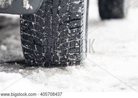 Close Up Winter Studded Tires Of A Car On The Road Covered By Snow And Ice Driving In Extreme Cold T