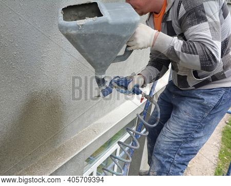 Kyiv, Ukraine - February 08, 2021: House Facade Renovation. A Man Is Applying Stucco, Texture Coatin
