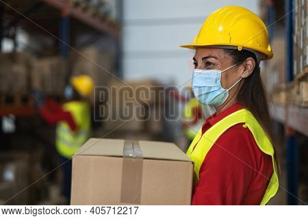 Latin Woman Working In Warehouse Loading Delivery Boxes While Wearing Face Mask During Corona Virus