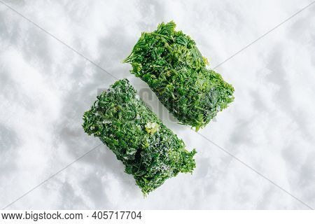 Two Frozen Parsley Green Briquettes On A Grinded Ice. Top View.