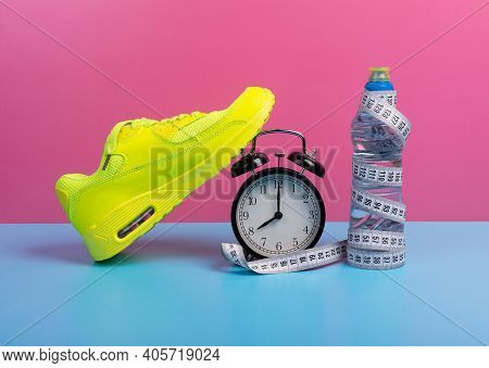 Fitness, Wellbeing And Home Or Gym Exercises Concept With Shoes,  Water Bottle Alarm Clock And Measu