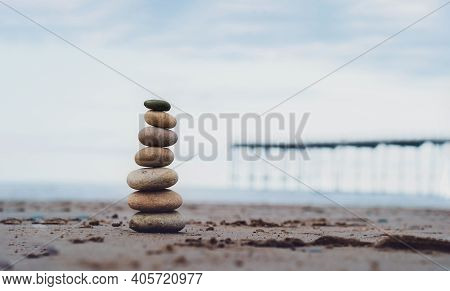 Pebble Tower By The Seaside With Blurry Pier Down To The Sea, Stack Of Zen Rock Stones On The Sand,