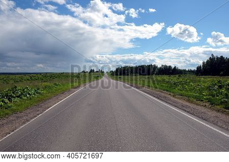 Landscape With Direct Empty Suburban Road Through The Field And Forest With Stormy Clouds On One Sid