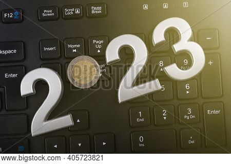 Black Keyboard. Close-up. On It Are Laid Out Numbers Of Metal 2023 In The Center Of The Coin 2 Euro