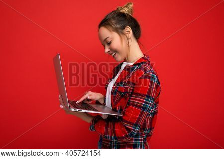 Side Profile Photo Of Pretty Smiling Young Woman Holding Netbook Looking At Screen Typing On Keyboar