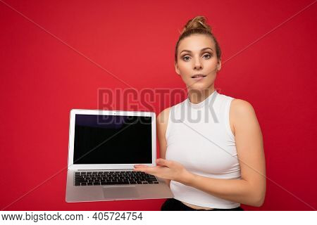 Photo Of Beautiful Blond Young Woman With Gathered Hair Looking At Camera Holding Computer Laptop Wi