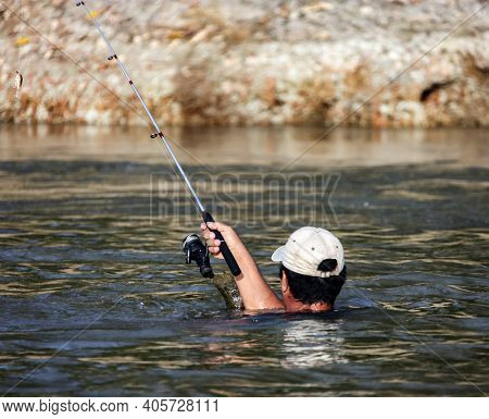 Head And Hand Of A Fisherman With A Spinning Rod Above The Water While Fishing In A Tropical River.