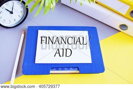 Financial Aid Text Written On Whie Paper Above On Notebook, Business Concept To Illustrate Official