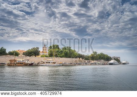 Pier With Moored Sailboats And Ferries In Zadar Bay. Fortification, Walled Old Town And Belltower Of