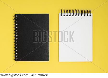 Two Notepads On A Yellow Background. Overhead View Of Open And Closed Notepads With Copy Space.