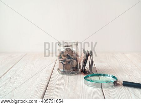 Money In A Glass Jar And A Magnifying Glass Next To The Jar On A Light Background.