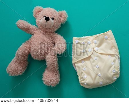 Reusable Cloth Baby Diaper. Eco Friendly Nappy And Teddy Bear On Green Background.