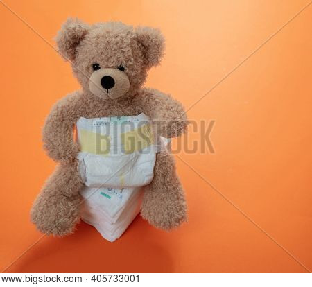 Baby Diapers And Teddy On Orange Color Background.