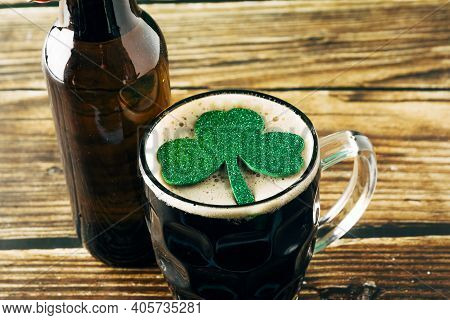 Close-up Of The Foam Of A Dark Beer With A Shiny Clover Leaf, Served In A Mug On A Wooden Table. St.