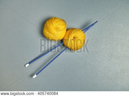 Blue Spokes And Yellow Wool Yarn On A Gray Surface