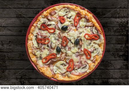 portrait of pizza with cheese and olive seed and dark grey background. Pizza is a savory dish of Italian origin consisting of a usually round, flattened base of leavened wheat-based dough topped with tomatoes, cheese, and often various other ingredients.