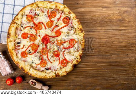 portrait of pizza with cheese and olive seed and brown wooden background. Pizza is a savory dish of Italian origin consisting of a usually round, flattened base of leavened wheat-based dough topped with tomatoes, cheese, and often various other ingredient