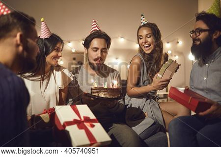 Young Birthday Man Makes A Wish And Blows Out The Candles On The Cake Surrounded By His Friends.