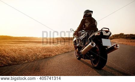 Handsome Motorcyclist In Leather Jacket And Helmet At Sunset On The Road In Warm Sun Rays