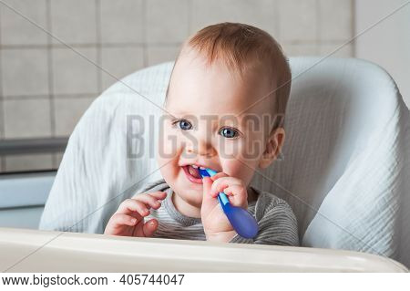 Cheerful Child Eats Food With Spoon. Close Up Portrait Of Happy Boy In High Chair. Complementary Fee