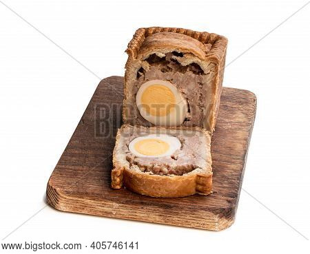 Traditional  English Savoury Gala Egg Pork Pie On Cutting Board Isolated On White