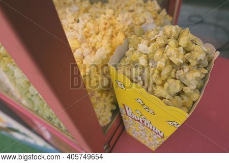 Delicious Popcorn Inside Box With Popcorn Text Displayed And Placed On Popcorn Stand Ready To Sell