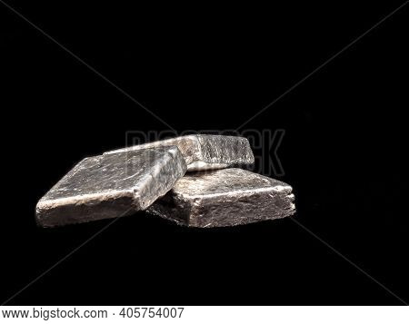 Three Silver Bars Or Ingots Stacked On A Black Background.