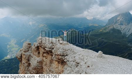 Fantastic Landscape Of Mountain Rocks And Woman Standing On The Top With Outstretched Hands. Freedom