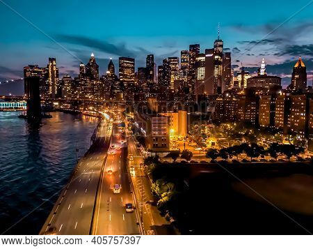 New York City Manhattan Skyscrapers And Brooklyn Bridge Over Hudson River Illuminate With Lights And