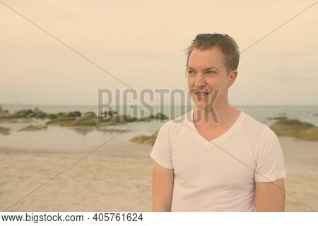Young Happy Handsome Man Smiling While Thinking At The Public Beach Of Hua Hin In Thailand
