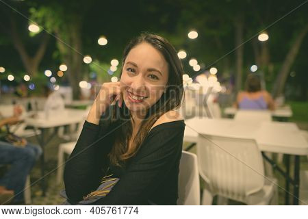 Young Happy Beautiful Asian Woman Smiling While Sitting At The Night Market Of Hua Hin In Thailand