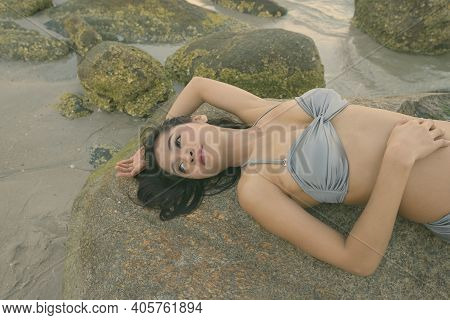 Young Beautiful Asian Woman Thinking While Lying Down And Posing On The Rocks Of Public Beach In Hua