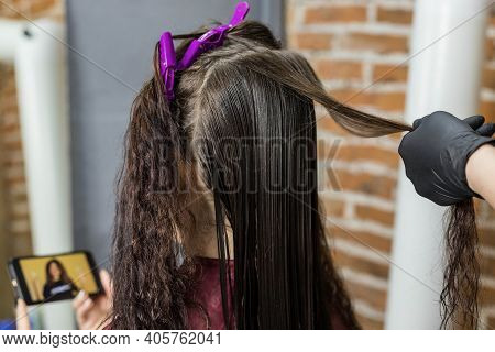A Young Woman Watches A Video On Her Phone While Sitting In A Hair Salon For A Keratin Hair Straight