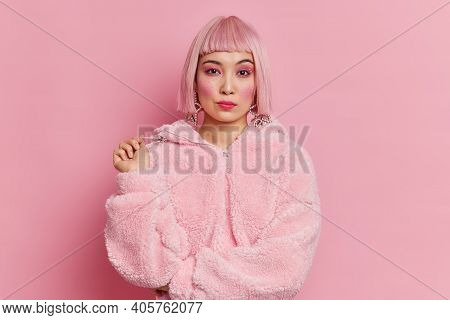 Serious Pretty Asian Woman With Trendy Pink Hair Dressed In Winter Coat Has Bright Vivid Makeup Pose
