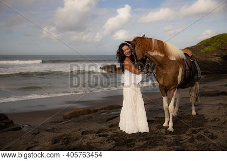 Happy Smiling Woman Leading Horse By Its Reins. Horse Riding On The Beach. Human And Animals Relatio