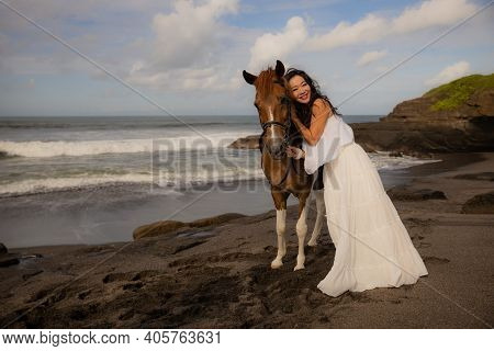 Beautiful Smiling Woman Leading Horse By Its Reins. Cuddling Horse. Love To Animals. Asian Woman Wea