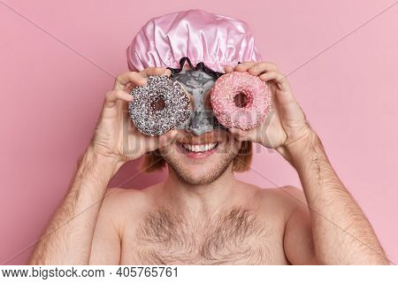 Cheerful Young Guy Covers Eyes With Sweet Delicious Doughnuts Wears Water Proof Shower Cap Applies C