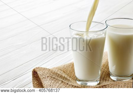 Two Glasses With Pouring Milk On White Wooden Table With Burlap Tablecloth