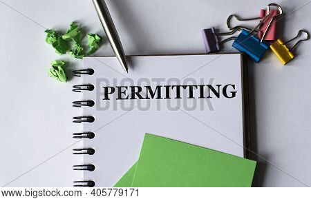 Permitting - Word In A Notebook On A White Background With A Pen, Green Pieces Of Paper And A Cactus