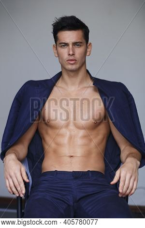 Closeup Frontal Portrait Of Young Confindence Handsome Young Man With Naked Torso, Over Grey Backgro