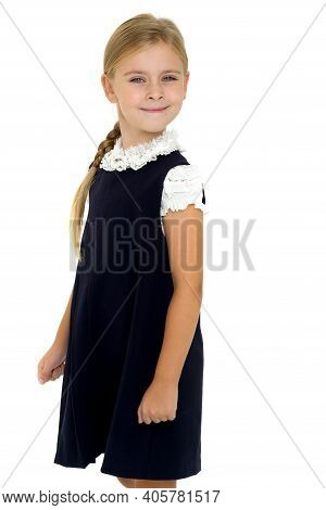 Charming Smiling Girl Posing In School Uniform. Cheerful Blonde In A White Blouse And A Blue Dress.